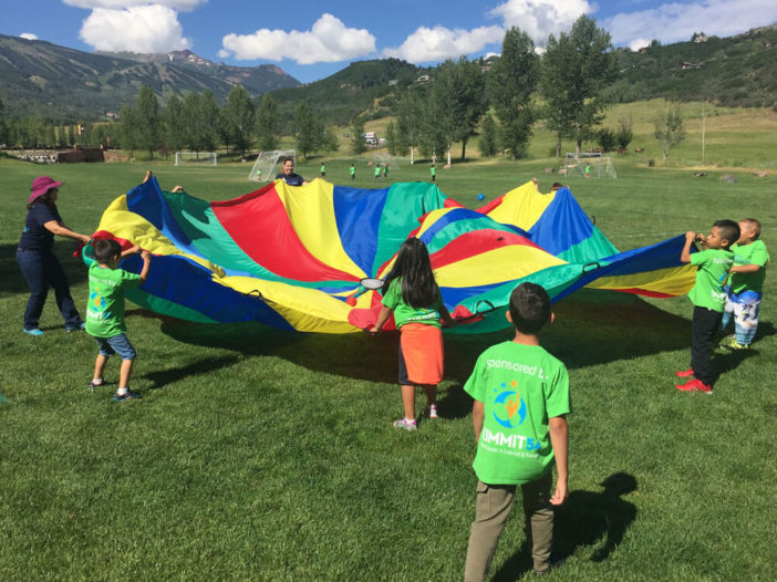 Summer Advantage students outside playing with a parachute